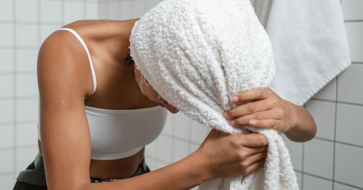 girl in bathroom wrapping her hairs in towel